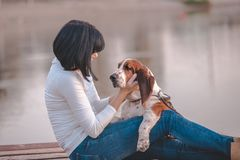 Woman sitting next to the river and hugging her dog Basset Hound. Portrait of beautiful young woman sitting next to the river and hugging her dog Basset Hound stock photos