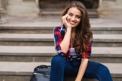 Portrait of a beautiful young woman sitting on stairs outdoors beautiful young woman smiling Stock Photos
