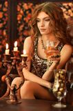 Beautiful young woman sitting in vintage chair with glass of cha. Portrait of beautiful young woman sitting in vintage chair with glass of champagne Stock Photography