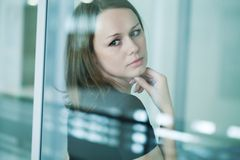 Sad woman at the window Stock Photos
