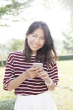 Portrait of beautiful young woman and smart phone in hand smilin Stock Photography