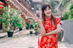 Portrait beautiful young woman smile wear cheongsam deep red dress holding a fan looking camera. Festivities and Celebration. Concept stock photo
