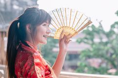 Portrait beautiful young woman smile wear cheongsam deep red dress holding a fan looking outside. Festivities and Celebration. Portrait beautiful young woman royalty free stock photo