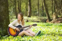 Portrait of a beautiful young woman smiling and playing guitar outdoors Royalty Free Stock Images