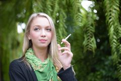Portrait of a beautiful young woman smoking stock image