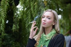 Portrait of a beautiful young woman smoking royalty free stock images