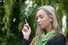 Portrait of a beautiful young woman smoking stock photos
