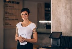Female waitress working in a restaurant. Portrait of beautiful young woman standing in a cafe with a digital tablet. Female waitress working in a restaurant royalty free stock photo