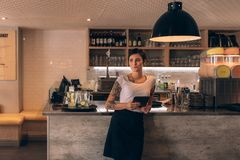 Cafe owner standing at the counter. Portrait of beautiful young woman standing by coffee shop counter. Woman cafe owner standing with a digital tablet stock images