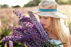 Portrait of a beautiful young woman in a straw hat with a bouquet of plucked lupins stock photography
