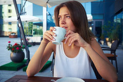 Portrait of beautiful young woman in street café drinking coffe Royalty Free Stock Image
