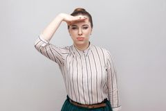 Portrait of beautiful young woman in striped shirt and green skirt with makeup and collected ban hairstyle, standing and holding stock image