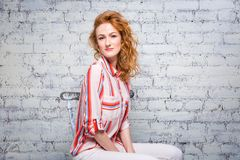 Portrait Beautiful young woman student with red curly hair and freckles on her face sitting on a wooden chair on a brick wall back. Ground in gray. Dressed in a stock photography