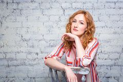 Portrait Beautiful young woman student with red curly hair and freckles on her face sitting on a wooden chair on a brick wall back. Ground in gray. Dressed in a royalty free stock photo