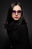 Portrait of a beautiful young woman in sunglasses. On black background Stock Photo