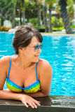 Portrait of a beautiful young woman in sunglasses in the pool Stock Photos