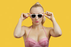 Portrait of a beautiful young woman in sunglasses puckering lips over yellow background Stock Image