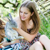 Portrait of beautiful young woman sweet smiling girl with a rabbit in the garden on summer green outdoors background Stock Photos