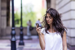 Portrait of beautiful young woman talking on the phone outdoor Stock Photography