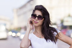 Portrait of beautiful young woman talking on the phone outdoor Stock Images