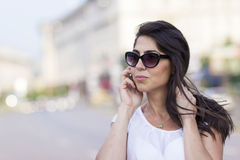 Portrait of beautiful young woman talking on the phone outdoor Royalty Free Stock Images
