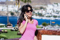 Portrait of beautiful young woman talking on the phone outdoor on a sea background Royalty Free Stock Image