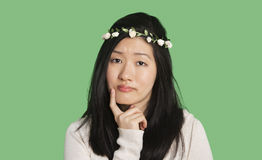Portrait of a beautiful young woman thinking with hand on her chin over green background Royalty Free Stock Photo