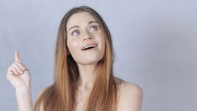 Portrait of a beautiful young woman thinking, isolated on grey background. Young beautiful woman with perfect skin and face over grey background having an idea stock video footage