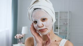 Portrait of beautiful young woman fixing rejuvenating cosmetic white tissue mask on face. Portrait of beautiful young woman with towel on the head fixing stock footage