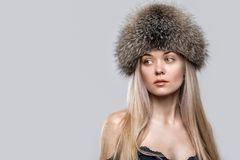 Portrait of a beautiful young woman in a trendy fur hat. Female face closeup Royalty Free Stock Photography