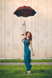Portrait of beautiful young woman with umbrella. Portrait of beautiful red-haired young woman with umbrella Stock Photo
