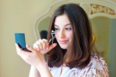 Portrait of  beautiful young woman using eyelash curler Royalty Free Stock Photos