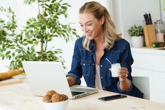 Beautiful young woman using her laptop and eating yogurt at home. Portrait of beautiful young woman using her laptop and eating yogurt at home Stock Photography