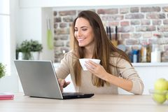 Beautiful young woman using her laptop in the kitchen. Royalty Free Stock Photo