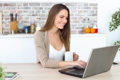 Beautiful young woman using her laptop in the kitchen. Stock Photography
