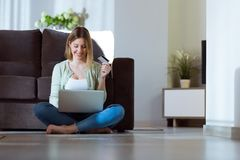 Beautiful young woman using her laptop for shopping online at home. Stock Photos