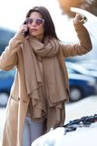 Beautiful young woman using her mobile phone calls for assistance for car. Royalty Free Stock Photo