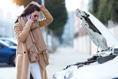 Beautiful young woman using her mobile phone calls for assistance for car. Stock Photo