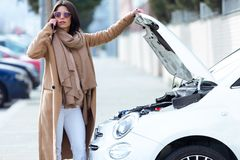 Beautiful young woman using her mobile phone calls for assistance for car. Portrait of beautiful young woman using her mobile phone calls for assistance for car stock image