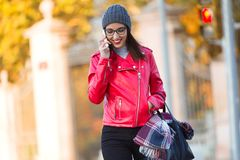 Beautiful young woman using her mobile phone in the city. Royalty Free Stock Photo