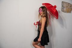 Portrait of beautiful young woman, with venetian carnival red mask, with red umbrella. stock photo