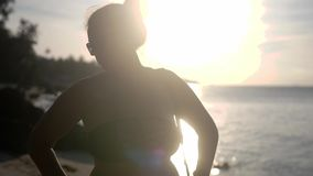 Portrait of beautiful young woman wearing bikini and sunglasses stands on tropical beach with sun rays shining against a. Sunny sky. Travel and lifestyle stock footage