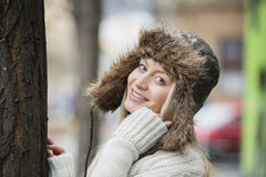 Portrait of beautiful young woman wearing fur hat outdoors Stock Images