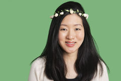 Portrait of a beautiful young woman wearing a hair wreath over green background Stock Photo