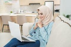 Beautiful young woman wearing hijab watching film on laptop