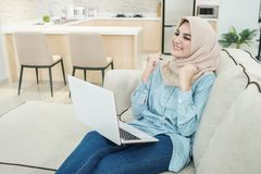 Beautiful young woman wearing hijab watching great movies on lap