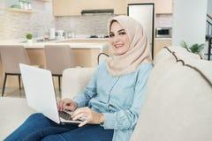 Beautiful young woman wearing hijab working on laptop
