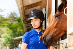 Beautiful young horsewoman standing by bay horse Stock Images