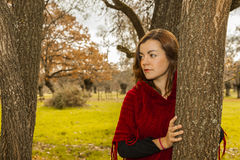 Portrait beautiful young woman wearing red wool poncho looking d Stock Photos