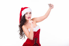 Portrait of beautiful young woman wearing santa claus clothes with smartphone making selfie. Isolated on white. Portrait of beautiful sexy girl wearing santa Royalty Free Stock Image